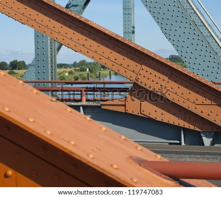 orange painted steel structure of a bridge with bolts and nuts