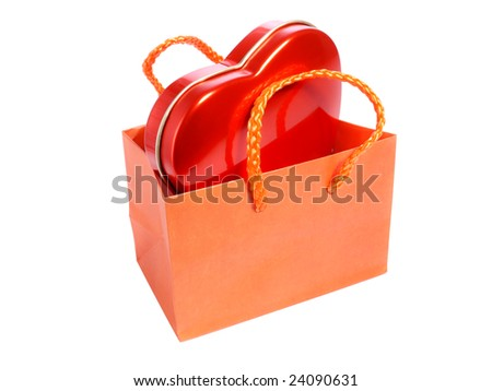 Orange paper bag with red heart candy box over white background