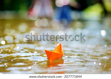 Orange paper boat with a white flag floating on a river