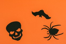 Orange paper Halloween background with black decorative bat, spider and skull.