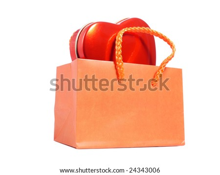 Orange paper shopping bag with red heart candy box over white background
