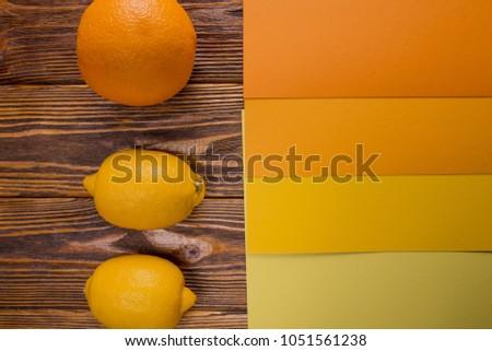 orange, paprika, lemon on a wooden background with a palette, fl