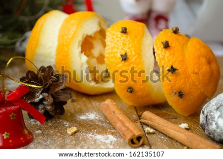 Orange peel, cinnamon stick, pine cone and spices among christmas decorations on wooden table
