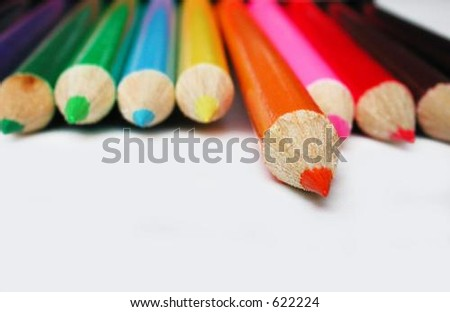 orange pencil crayon isolated from other colorful pencil crayons