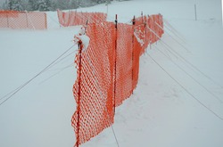 orange perforated plastic PE foil barriers against snow in mountain areas. slow down the speed of snow, forming tongues and dune barriers on the highway roadway. It protects windbreak during blizzard