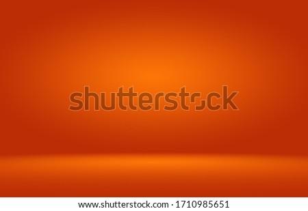 Orange photographic studio background vertical with soft vignette. Soft gradient background. Painted canvas studio backdrop.