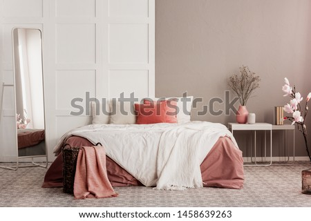 Orange pillows on white king size bed in fashionable female bedroom