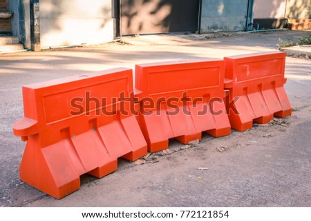 Orange plastic barrier lined up on the road #772121854