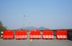 Orange plastic blocks are setting up for road side protection.  Caution, prohibition and traffic regulations.