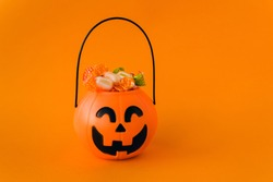 Orange plastic candy basket in the shape of a pumpkin jackolantern on a orange background. Place for your text, layout for advertising.