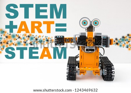 Orange plastic robot programmable on Scratch. STEM plus art is equal to STEAM. Science, technology, engineering, art, mathematics. The concept of new methods of teaching children and teenagers.