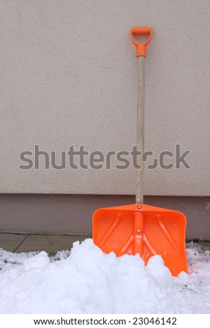 Orange plastic snow shovel against building wall - stock photo