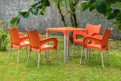 Orange plastic table and chairs in the summer garden
