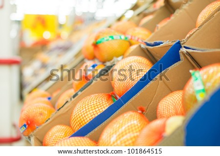 Orange pomelos in boxes in supermarket