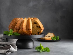 Orange pound cake with dried cherry decorated with fresh mint leaves on black wooden plate. Grey concrete background. Copy space. Homemade easy cooking dessert.