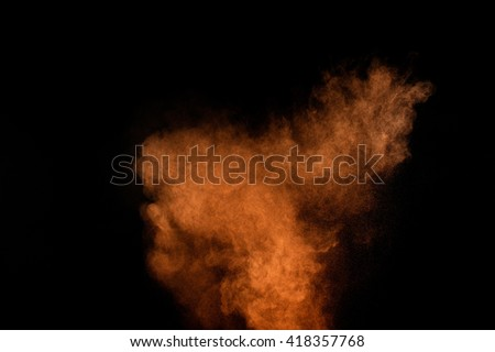 Orange powder explosion on black background. Colored powder cloud. Colorful dust explode. Paint Holi. #418357768