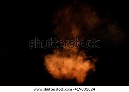 Orange powder explosion on black background. Colored powder cloud. Colorful dust explode. Paint Holi. #419081824