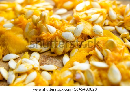orange pulp of ripe pumpkin with white seeds on a wooden background.