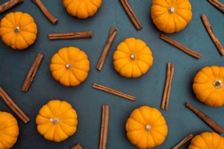 Orange pumpkin and cinnamon stick on stone background. Top view of flat lay style food and spice for menu, banner, magazine, cook book and web advertising.
