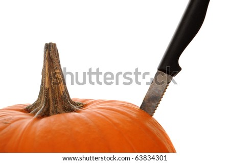Orange pumpkin  isolated on a white background with a knife stabbed in the side to demonstrate a pumpkin carving theme.