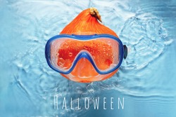 Orange pumpkin swimmer in a mask in blue water. Halloween concept.