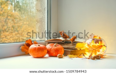 orange pumpkins, books and candle lantern on window sill. autumn seasonal composition. fall time, thanksgiving and halloween concept. home comfort. copy space