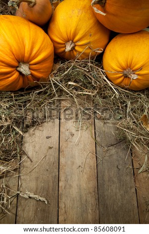 orange pumpkins lay on a wooden background with a straw