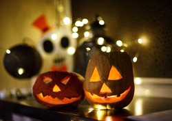 orange pumpkins with scary faces and candles lies on the dark background. Halloween celebration, home decoration concept