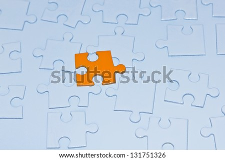 Orange puzzle piece and many white puzzle pieces