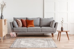 Orange, red and beige pillows on grey comfortable couch in chic living room interior