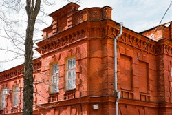 Orange red brick wall of an old building corner and huge windows. Architecture . Architect. History. Heritage. Design. Grunge urban. Industrial style. Orange brick wall