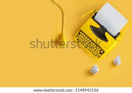 Orange retro typewriter on paper background with light bulb, brainstorming writers block