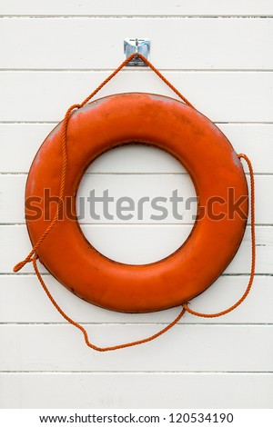 Orange ring buoy hanging on an exterior wall of white painted wood siding