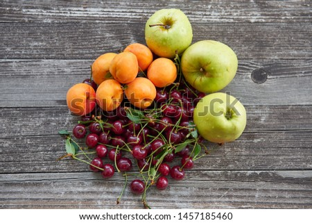 Orange riped peaches, green apples, red gooseberries and sour cherries just after harvest on old wooden table in the garden. Summer seasonal fruits full of nutrients and vitamins for raw diet snack.