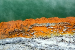 Orange rock in hot water from which steam rises, deposits of minerals along the shore of the spring