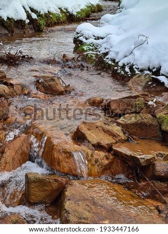 Orange rocks in river creek water. Forest river creek rocks. Rocks in creek water. Forest rocks in cold creek. winter landscape
