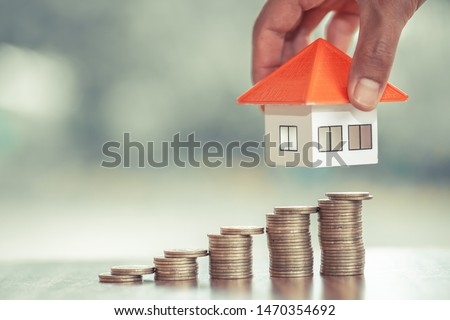 Orange roof house and coin staircase. Hands are going to put houses on coins, real estate concepts, mortgages and investments, save money or invest for future homes, areas to enter text.