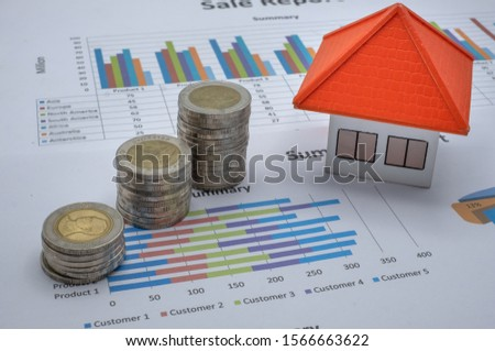 Orange roof house On a graph. Stacks of coins. House and property concept Tax finance chart. Movable property, mortgages and real estate investments for savings or investments for homes.