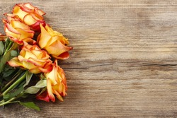 Orange roses on wooden background, copy space