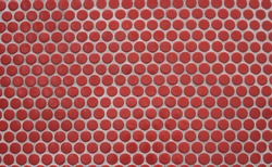 Orange round glazed mosaic tiles with cement grout. Penny round tiles
