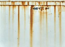 Orange rust streaks down a white wall
