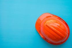 Orange safety helmet on blue background - Construction industry concept