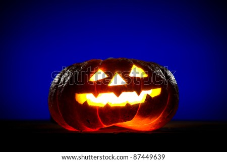 Orange scarry pumpkin with burning eyes, nose and mouth on blue background in the dark