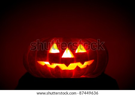 Orange scarry pumpkin with burning eyes, nose and mouth on dark red background in the dark