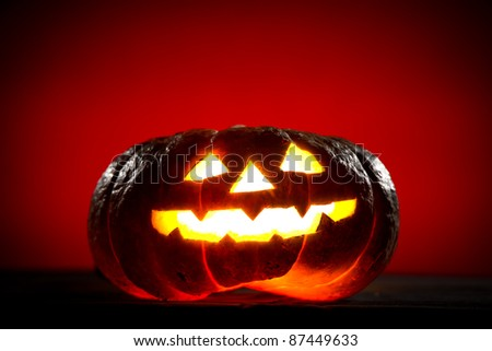 Orange scarry pumpkin with burning eyes, nose and mouth on red background in the dark