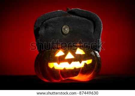 Orange scarry pumpkin with burning eyes, nose and mouth with winter military hat on red background in the dark