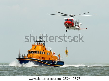 orange sea rescue boat at sea off south coast of Britain man being winched to emergency rescue helicopter #352442897