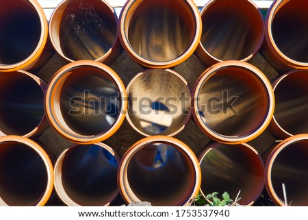 orange sewer pipes at a construction site. Underground orange plastic pipes. Stacked PVC orange pipes. Stock photo ©