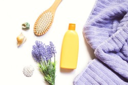 Orange shampoo package, purple lavender flowers, wooden comb and lilac towel. Flat lay photography natural organic hair care cosmetic products. Beauty still life photo