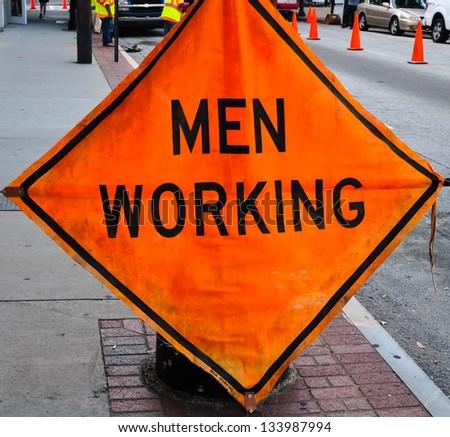 orange sign indicating men working in a street scene